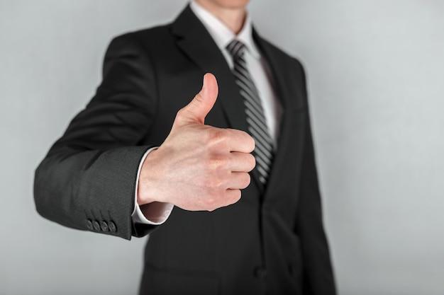 親指を立てるビジネスマンのクローズアップ