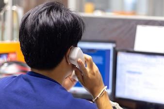 Closeup of businessman turn-back making a phone call on landline telephone