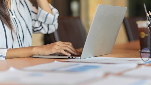 Крупный план руки бизнесвумен, печатающей на ноутбуке с финансовыми документами и канцелярскими принадлежностями на столе