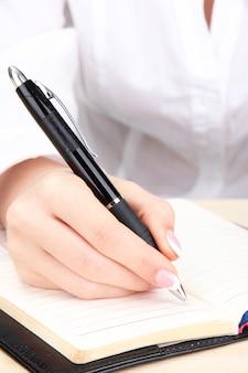 紙に書く実業家の手のクローズ アップ