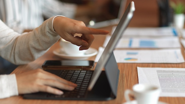 금융 서류와 함께 노트북에 가리키는 사업가 손의 근접 촬영