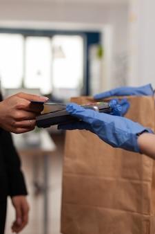 테이크 아웃 점심 시간 동안 pos 비접촉 서비스를 사용하여 신용 카드로 테이크 아웃 음식 주문을 지불하는 사업가의 근접 촬영