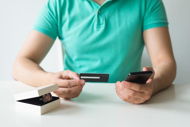 Крупный план покупателя держа кредитную карточку и smartphone