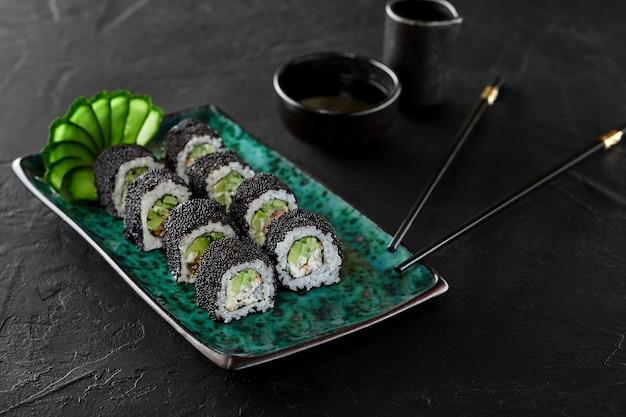 カリフォルニアロールのクローズアップは、タイガーエビ、アボカド、キュウリ、日本のマヨネーズを詰めた黒いトビコキャビアで、伝統的に醤油を添えています。本物の食品のコンセプト
