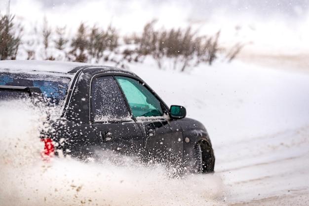 雪に覆われた道路で冬に戻って車のクローズアップ。