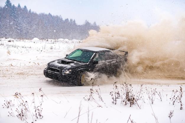 雪に覆われた道路で冬に漂う車のクローズアップ