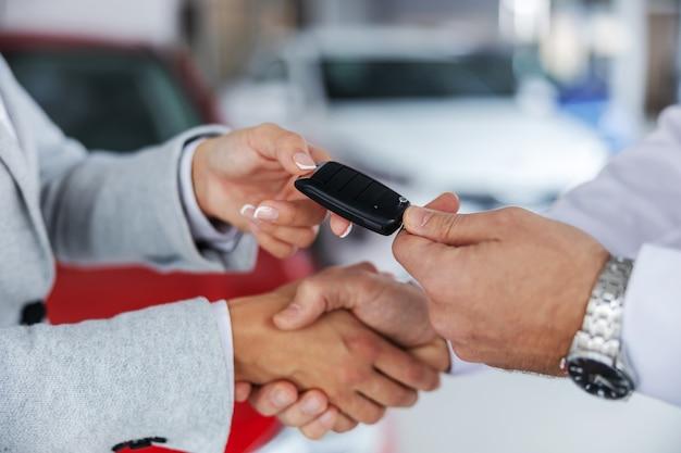 자동차 판매자와 자동차 살롱에 서있는 동안 악수하는 구매자의 근접 촬영. 판매자가 구매자에게 자동차 키를 전달합니다.