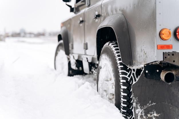 雪に覆われた道路上の冬の車のタイヤのクローズアップ。極寒の冬用タイヤ。輸送の概念