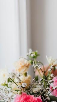 Крупным планом гвоздики в вазе у окна