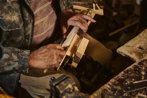 Крупный план рук плотника в работе над деревянными предметами в мастерской. ремесленник делает деревянные игрушки ручной работы. мастер в действии