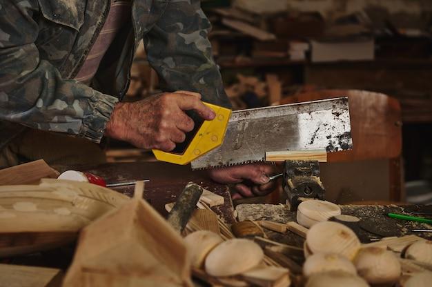 Крупным планом - плотник, распиливающий дерево пилой в своей мастерской для изготовления изделий ручной работы из дерева.