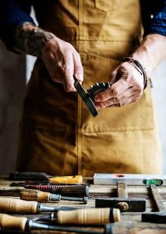 Крупным планом плотник, работающий со своими инструментами