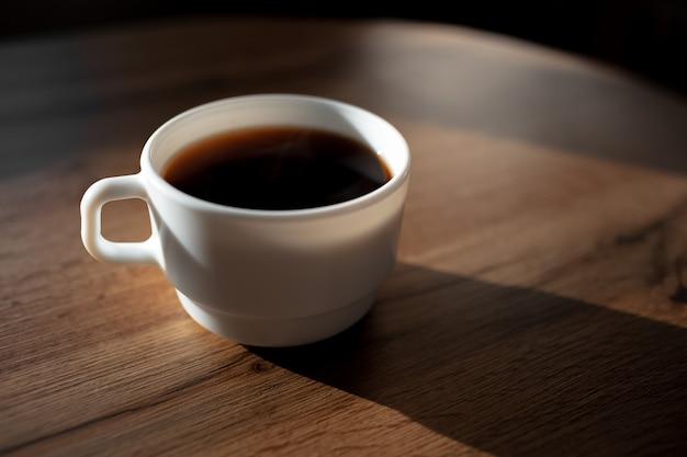 나무 테이블에 세라믹 커피 컵의 근접 촬영입니다. 프리미엄 사진