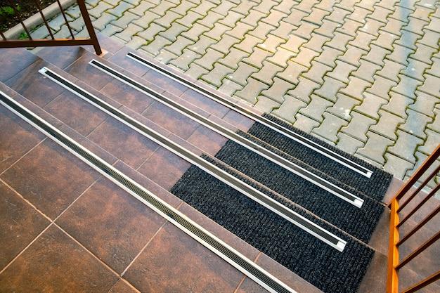 その上にゴム製の滑り止めストライプでポーチの階段を覆うセラミックタイルのクローズアップ。