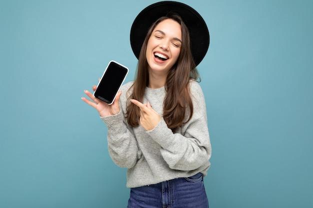 Крупным планом очаровательная молодая счастливая женщина в черной шляпе и сером свитере смеется