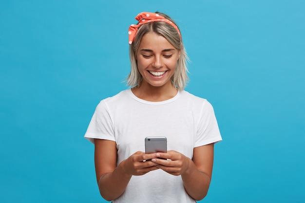 陽気な美しい金髪の若い女性のクローズアップは白いtシャツを着ています