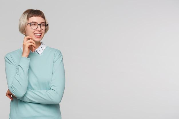 陽気な美しい若い女性のクローズアップは青いスウェットシャツを着ています