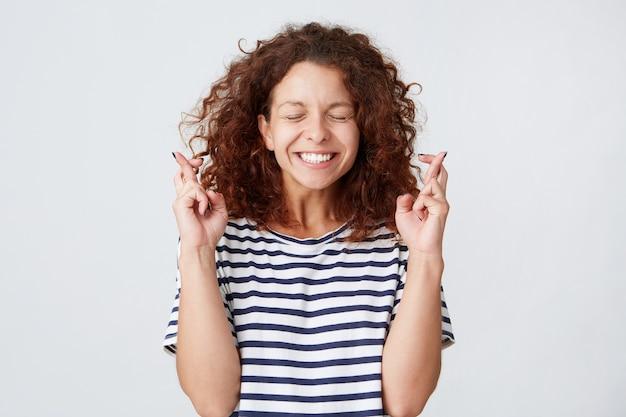 곱슬 머리와 닫힌 눈을 가진 쾌활한 흥분된 젊은 여자의 근접 촬영 스트라이프 티셔츠를 착용