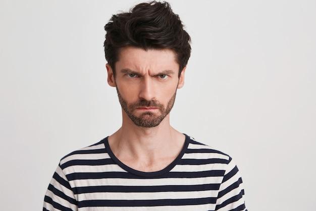 Крупным планом веселый красивый молодой человек с щетиной в полосатой футболке чувствует себя счастливым изолированным на белом