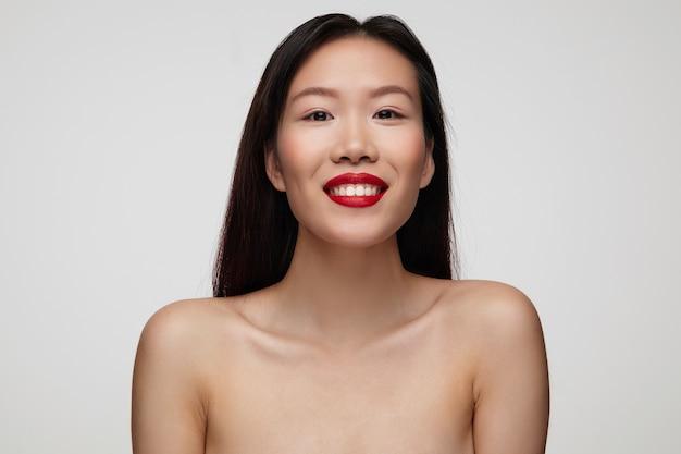 쾌활한 젊은 사랑스러운 갈색 머리 여자의 붉은 입술이 행복하게보고 넓게 웃고, 흰 벽 위에 포즈를 취하는 동안 좋은 분위기에있는 것의 근접 촬영