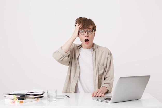 Крупным планом веселый молодой студент-мужчина с подтяжками носит бежевую рубашку изучает с помощью портативного компьютера и ноутбуков, сидя за столом, изолированным над белой стеной