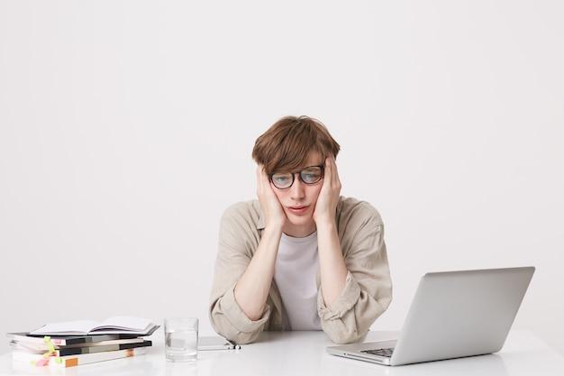 中かっこで陽気な若い男子学生のクローズアップは、白い壁の上に隔離されたテーブルに座っているラップトップコンピューターとノートブックを使用してベージュのシャツの研究を着ています
