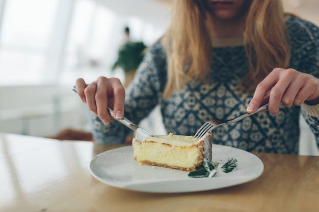 Крупным планом чизкейк и лист мяты посыпали сахарной пудрой на белой тарелке.
