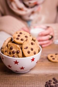 バックグラウンドでホットドリンクグラスを保持している女性の手でテーブルの上の星のボウルにチョコレートチップクッキーのクローズアップ