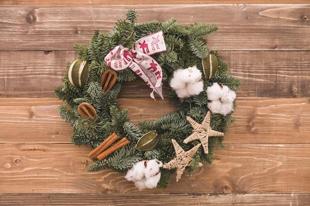 Крупным планом рождественский венок с ушками из хлопка корицы и украшениями из лент на деревянном фоне