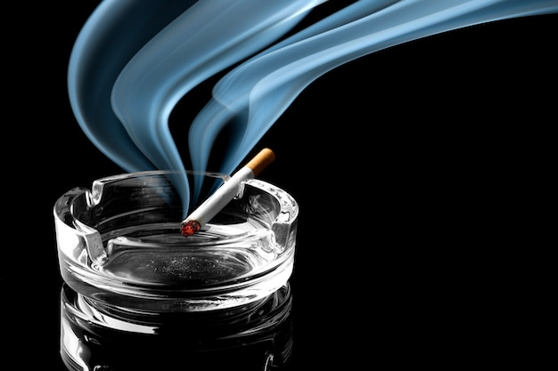 煙の美しい一片と灰皿上のタバコのクローズアップ