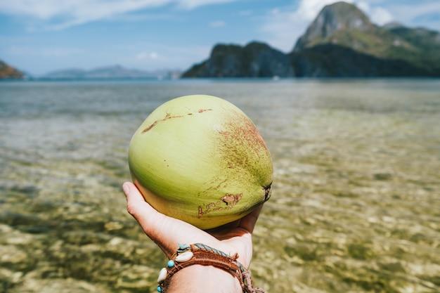 エキゾチックな海の島々に対する男性の手でココナッツのクローズアップ