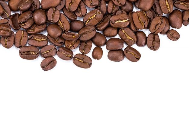 白い背景の上のコーヒー豆のクローズアップ。コピースペース
