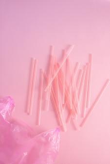 ピンクの背景に分離されたリサイクル可能な使い捨てカトラリー汚染ジャンクコンセプトとしてピンクのゴミ袋にカラフルなプラスチック廃棄物のクローズアップ