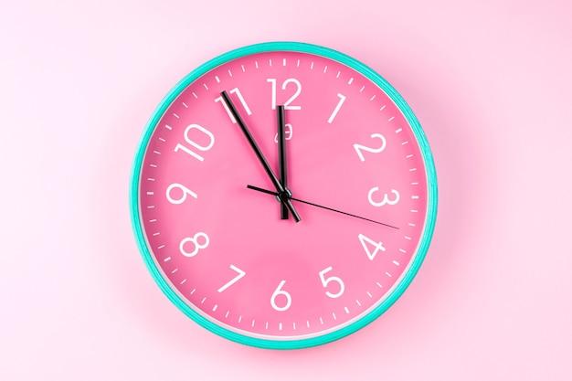 분홍색 배경에 화려한 벽 시계의 근접 촬영입니다. 플라스틱 벽시계의 미니멀리스트 평신도 이미지.