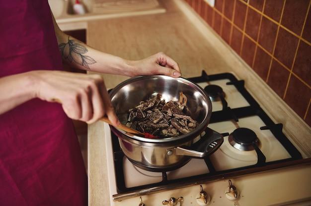 木製のスパチュラを保持し、キッチンのストーブの水浴でチョコレートを加熱して溶かす菓子ショコラティエのクローズアップ