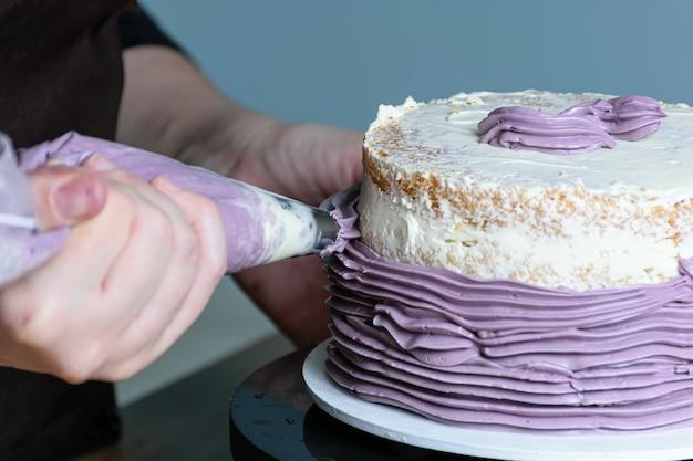 버터 크림을 입힌 주둥이와 케이크를 턴테이블에 올려놓는 제과점의 손을 클로즈업.
