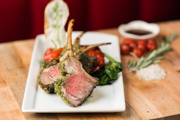 調理された牛肉のスパイスと背景をぼかした写真の緑と赤ピーマンのクローズアップ