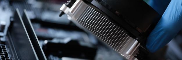 修理工の手でビデオカードを冷却するためのクーラーのクローズアップ