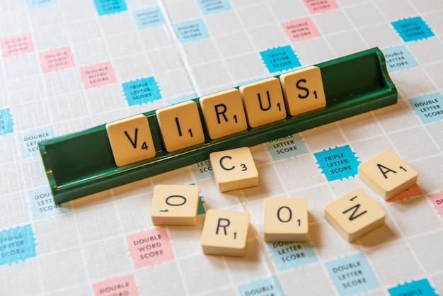 Крупный план слов короны и вируса, написанных на доске для скремблирования под огнями