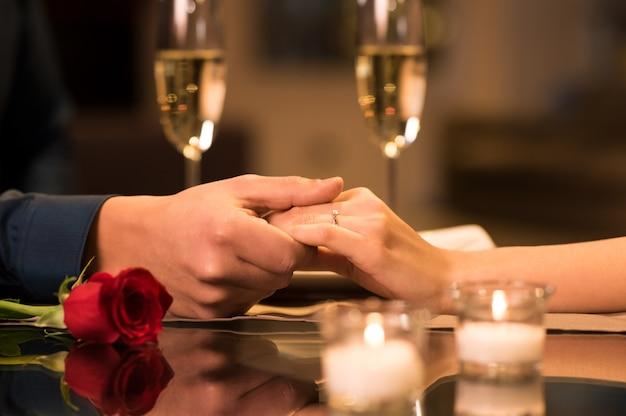 バックグラウンドでシャンパン2杯とレストランのテーブルの上のカップルの手のクローズアップ。