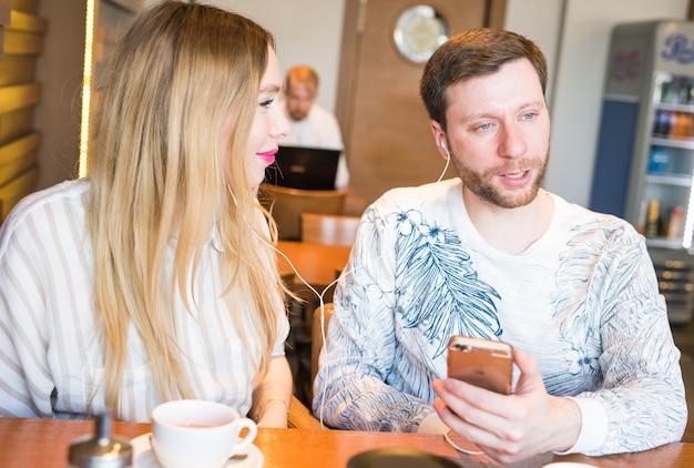 コーヒーバーで携帯電話で音楽を聴いているカップルのクローズアップ。ヘッドフォンで音楽を聴いている男性と女性。