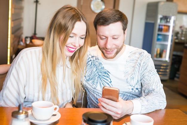 커피 바 남자와 여자 듣는 음악에서 휴대 전화로 음악을 듣고 커플의 근접 촬영