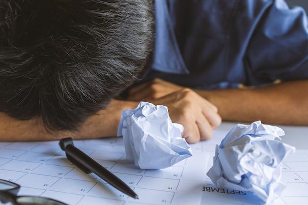 Макрофотография мятой бумаги на столе с несчастным бизнесменом отсутствие идей