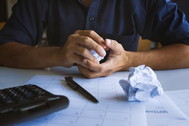 アイデアの不幸なビジネスマンの欠如とテーブルの上のしわくちゃの紙のクローズアップ