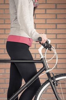 배경에 주황색 벽돌 벽 위에 맞춤형 픽시 자전거와 아름다운 젊은 낚시를 좋아하는 여성의 근접 촬영