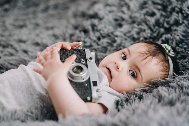 Slr 빈티지 필름 카메라를 들고 귀엽고 사랑스러운 아기의 근접 촬영