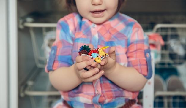 自宅の木の床の上で彼女の手でたくさんのヘアクリップで遊んでいるかわいい女の赤ちゃんのクローズアップ。ヘアクリップに選択的に焦点を当てます。