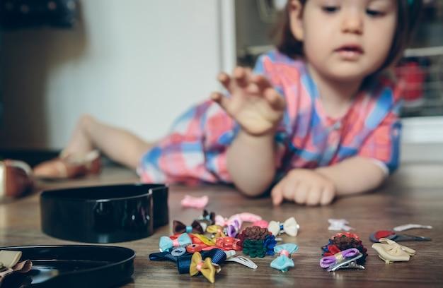집에서 나무 바닥에 누워 머리 클립 컬렉션을 가지고 노는 귀여운 아기 소녀의 근접 촬영. 헤어 클립에 선택적 초점입니다.