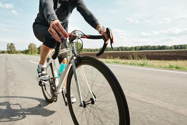 시골길에서 자전거를 타는 스포츠 의류를 입은 자전거 타는 사람의 근접 촬영