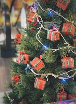 흐리게 반짝이 배경에 밝은 빨간색 볼 장식 크리스마스 트리의 근접 촬영.